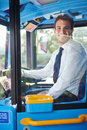 Portrait of bus driver behind wheel sitting down looking to camera smiling Stock Photography