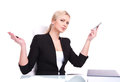 Portrait of business woman sitting on her desk beautiful young blond raising hands in surprise Royalty Free Stock Photography