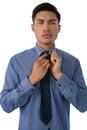 Portrait of businessman adjusting necktie Royalty Free Stock Photo