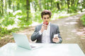 Businessman sitting at the office desk with laptop computer and cup of coffee use mobile phone in green forest park. Business conc Royalty Free Stock Photo