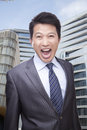 Portrait of businessman shouting and looking at camera buildings in the background Stock Photo