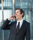 Portrait of a businessman talking and laughing on mobile phone close up Stock Photos