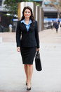 Portrait of businesswoman walking along street smiling Stock Images