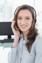 Portrait of businesswoman wearing headset in front of computer a bright office Stock Photos