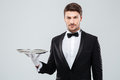 Portrait of butler in tuxedo holding empty tray Royalty Free Stock Photo
