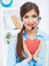 Portrait of call center smiling operator with phone headset iso on white office background hold red heart help concept Stock Photography