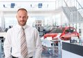 Portrait of car salesman in showroom looking at camera smiling Stock Image