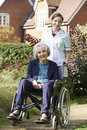 Portrait of carer pushing senior woman in wheelchair Stock Photos
