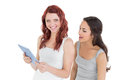 Portrait of casual female friends with digital tablet two young against white background Royalty Free Stock Photo