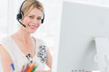 Portrait of a casual woman with headset using computer young in bright office Royalty Free Stock Image