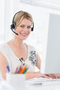 Portrait of a casual woman with headset using computer young in bright office Stock Image