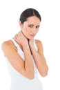 Portrait of a casual woman suffering from neck ache young over white background Royalty Free Stock Photo