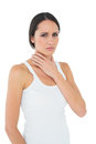 Portrait of a casual woman suffering from neck ache young over white background Stock Image