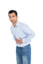 Portrait of a casual young man with stomach pain standing against white background Stock Image