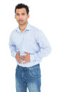 Portrait of a casual young man with stomach pain standing against white background Stock Images