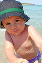 Portrait of caucasian happy baby boy in sea with hat stock photo Royalty Free Stock Photos