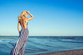 Portrait of charming blond long-haired woman in long black and white striped dress with naked back walking along the seaside Royalty Free Stock Photo