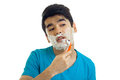 Portrait of a charming young man who tilted his head and gently shaves his beard machine