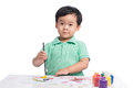 Portrait of cheerful asian boy painting using watercolors
