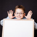 Portrait of cheerful boy pointing on white banner the black background Royalty Free Stock Photo
