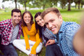 Portrait of cheerful college students in park group young the Royalty Free Stock Image