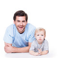 Portrait of cheerful father with baby little lying on the floor isolated on white Stock Photography