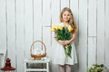 Portrait of cheerful little blonde girl with tulips bouquet on white wood background Royalty Free Stock Photo