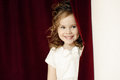 Portrait of cheerful pretty girl with ringlets posing on curtain background Royalty Free Stock Images