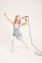 Portrait of a cheerful singing girls girl in denim clothes with microphone Stock Photography