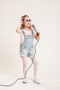 Portrait of a cheerful singing girls girl in denim clothes and sunglasses with microphone Royalty Free Stock Photo