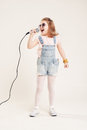 Portrait of a cheerful singing girls girl in denim clothes and sunglasses with microphone Royalty Free Stock Image