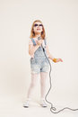 Portrait of a cheerful singing girls girl in denim clothes and sunglasses with microphone Stock Image