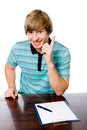 Portrait of a cheerful young man with a raised finger sitting behind desk isolated on white background Stock Photo