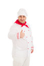 Portrait of chef showing thumb up sign wearing white uniform over background Stock Photos
