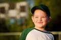 Portrait of child baseball player on field in front scoreboard Stock Images