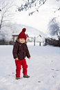 Portrait of child in brown jacket and red knitted hat and red tr trousers lots snow winter forest Stock Photography