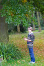 Portrait of child gathering colorful leaves in park a happy a beautiful Stock Photo