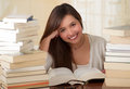 Portrait of clever student with open book reading it in college library smiling
