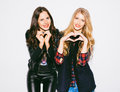 Portrait close up happy smiling two young womans showing heart sign gesture with hands nex to white background. Positive human emo Royalty Free Stock Photo