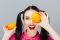 Portrait of comic happy girl holding orange near face gray background Royalty Free Stock Photo