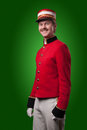 Portrait of a concierge porter in a red jacket on a green background Stock Photo