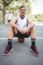 Portrait of confident basketball player sitting on ball Royalty Free Stock Photo