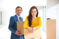 Portrait of confident businesswoman and male colleague with cardboard boxes in new office Royalty Free Stock Photo