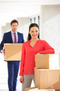 Portrait of confident businesswoman standing by stacked boxes with male colleague in background at office Royalty Free Stock Photo