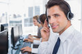 Portrait of a confident call center agent with his team working behind Royalty Free Stock Photos