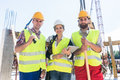 Portrait of confident colleagues posing during work break on construction site Royalty Free Stock Photo