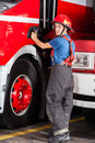 Portrait of confident firewoman standing by rear view firetruck at station Royalty Free Stock Photography