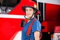 Portrait of confident firewoman wearing red helmet young against firetruck at station Royalty Free Stock Photo