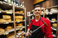 Portrait of confident male salesperson holding knife in cheese store Stock Photos