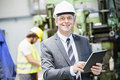 Portrait of confident mature businessman using digital tablet with worker in background at factory Royalty Free Stock Photo